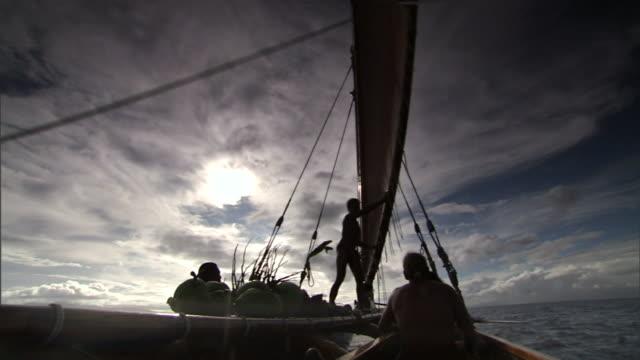 a polynesian man aboard a canoe points at something in the distance. - polynesiskt ursprung bildbanksvideor och videomaterial från bakom kulisserna