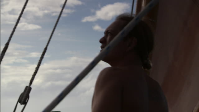 stockvideo's en b-roll-footage met a polynesian man looks out from aboard a canoe. - polynesische etniciteit