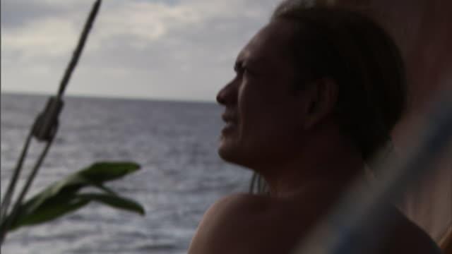 a polynesian man points into the distance from his spot on a canoe. - polynesiskt ursprung bildbanksvideor och videomaterial från bakom kulisserna