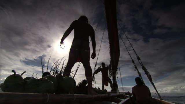 a polynesian man points into the distance while standing aboard a moving canoe. - polynesiskt ursprung bildbanksvideor och videomaterial från bakom kulisserna
