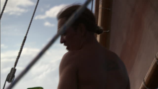a polynesian man stands in a canoe as it cruises through the pacific ocean. - polynesian ethnicity stock videos & royalty-free footage