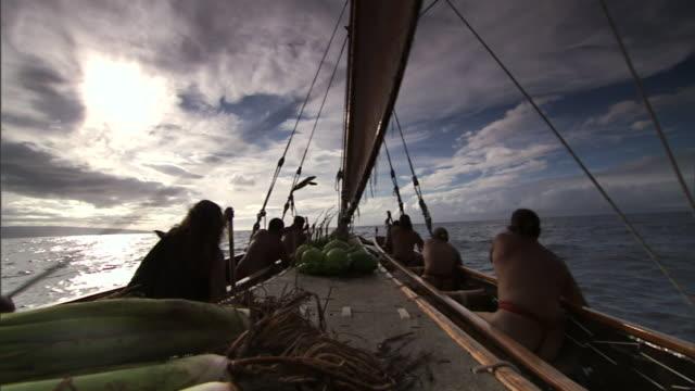 polynesian men navigate a canoe through the pacific ocean on their way to hawaii. - polynesiskt ursprung bildbanksvideor och videomaterial från bakom kulisserna