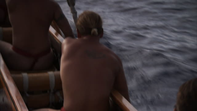 polynesian men row a canoe through the pacific ocean in pursuit of life in hawaii. - polynesian ethnicity stock videos & royalty-free footage