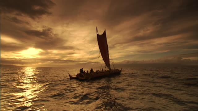 polynesian settlers sail at sunset en route to hawaii. - historische szene stock-videos und b-roll-filmmaterial