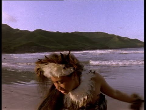 Polynesian woman performing Tropic Bird Dance waves lapping gently on shore in background