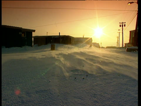 Pond Inlet reservation buildings at sunset as snow swirls snow covered reservation with mountain ranges in the background