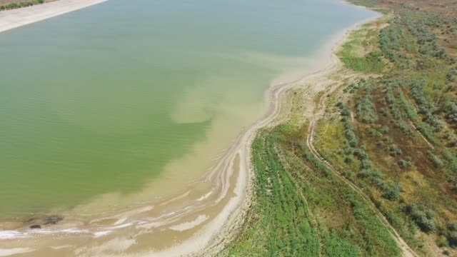 AERIAL: Pond with sandy shore in countryside