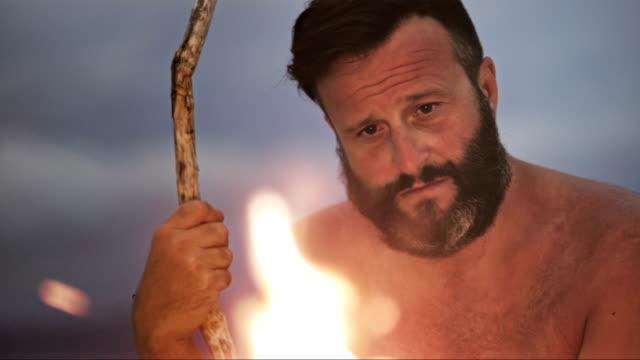 slo mo pondering mann auf einer insel an der feuerstelle - in den dreißigern stock-videos und b-roll-filmmaterial
