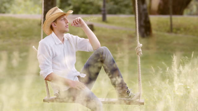 slo mo ds pondering young man sitting on a swing - grass stock videos & royalty-free footage