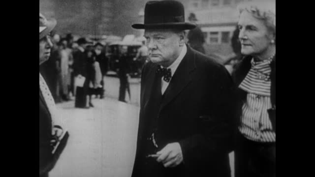 vídeos de stock e filmes b-roll de a ponderous prime minister neville chamberlain makes way for prime minister winston churchill and his wife clementine - 1939