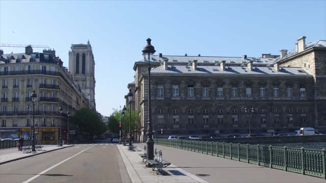 pont d'arcole with view of the towers of the notre dame de paris cathedral with only three people and a child on the street during the coronavirus... - four people stock videos & royalty-free footage
