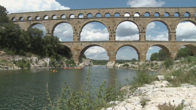 ws pont du gard, roman aqueduct, people canoeing on gard river in distance / languedoc-roussillon, france - arch stock videos & royalty-free footage