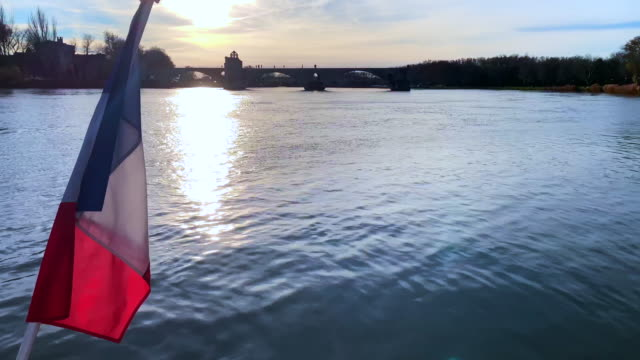 pont sant benezet over rhone river and french flag in sunset in avignon - rhone river stock videos & royalty-free footage