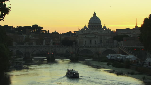 ws, ponte sant angelo over tiber river and st. peter's basilica in background, sunset, rome, italy - サンタンジェロ橋点の映像素材/bロール