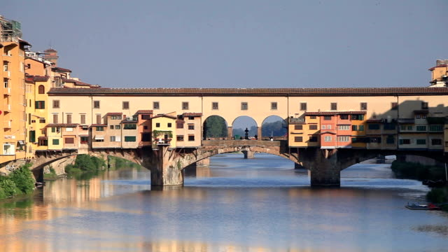 ponte vecchio over the river arno in the city of florence. the bridge dates from medieval times and now houses many jewelers, art dealers and souvenir shops. - ponte stock videos & royalty-free footage