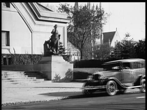 b/w 1928 pontiac car pulling up in front of building / industrial - 1928 stock-videos und b-roll-filmmaterial