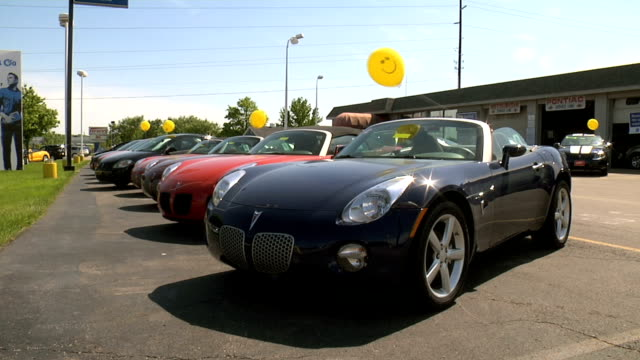 pontiac solstice front end parked on lawn between highway and dealer's lot / ws rear of dealership building / ws dealership front lot / ws row of... - pontiac stock videos and b-roll footage