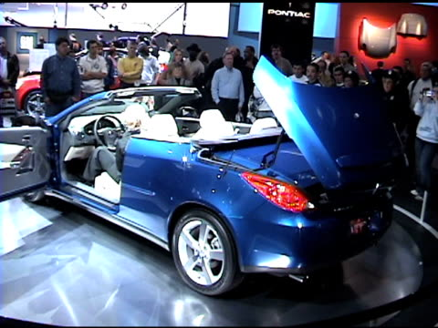 ws pontiac's retractable hardtop folding back and disappearing into trunk / ws ha convertible interior / ws front end of car revolving on turntable... - curious cumulus productions stock videos and b-roll footage
