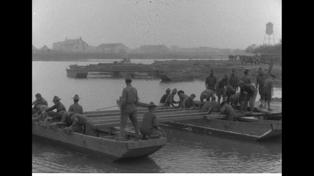 pontoon boats row across the rio grande river / men place planks over wooden supports between boats for the crossing platform / pan right of the... - pontoon bridge stock videos and b-roll footage