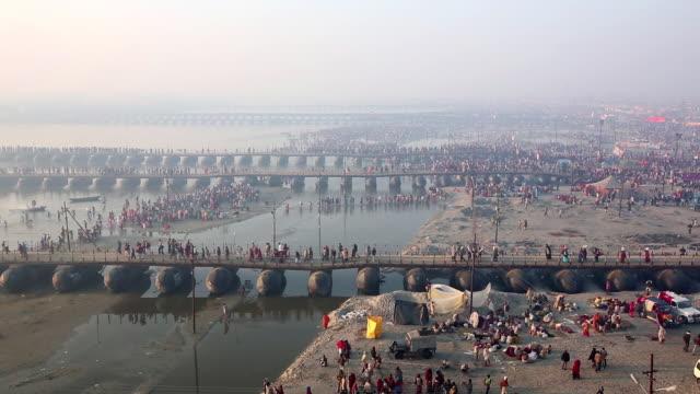 Pontoon bridges span shallow water as pilgrims cross and banks accommodate myriad activities. Kumbh Mela, India