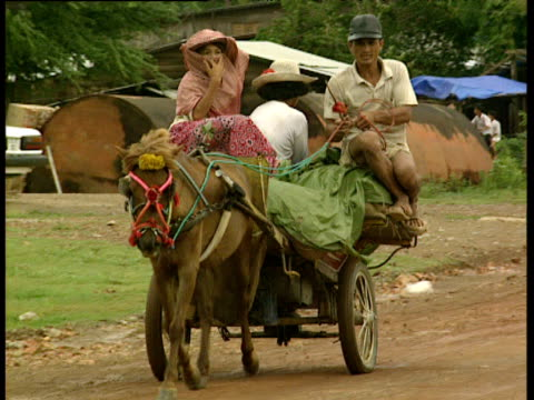 pony pulls cart carrying family and their goods cambodia - cambodia stock videos and b-roll footage