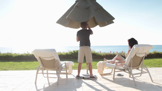 WS Pool attendant putting up parasol for guest at luxury resort