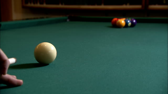a pool cue strikes the cue ball, knocking it into the racked billiard balls. - cue ball stock videos & royalty-free footage