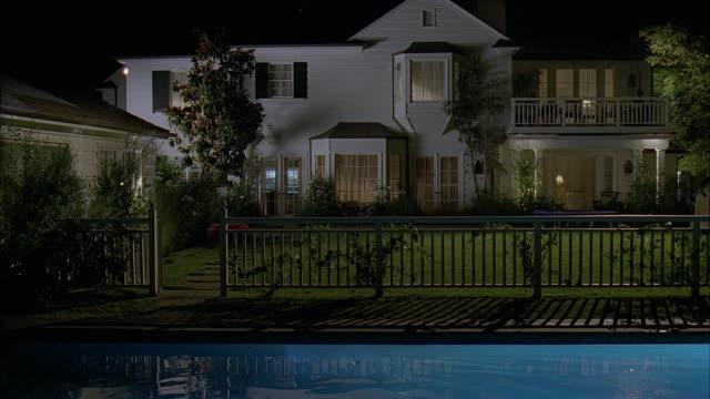 vídeos de stock, filmes e b-roll de ws pool in backyard of large suburban house at night / california, usa - janela saliente