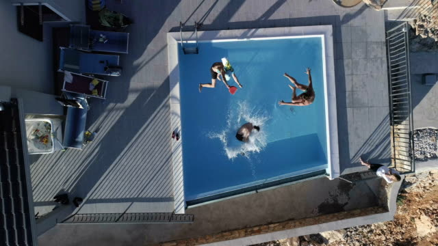 pool jumps. aerial view - three people stock videos & royalty-free footage