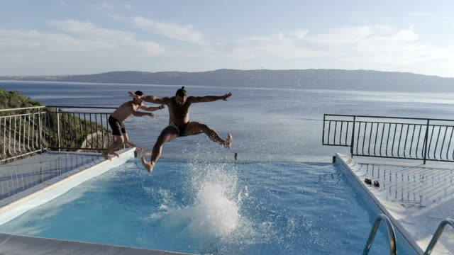pool jumps. aerial view - male friendship stock videos and b-roll footage