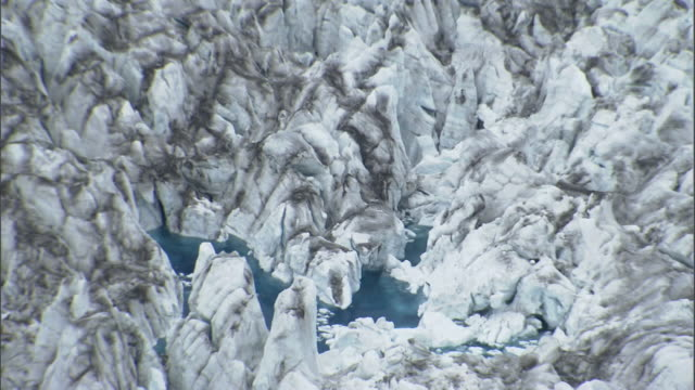 a pool of icy blue water nestles in the valleys of the columbia glacier. - columbia glacier stock videos & royalty-free footage