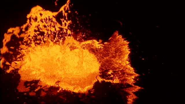 A pool of molten lava bubbles and splashes violently. Available in HD.