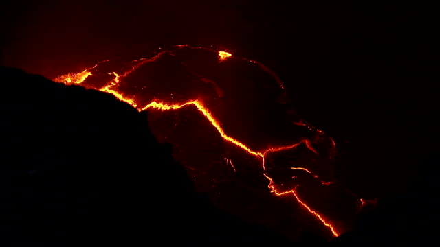 A pool of molten lava glows red at night. Available in HD.