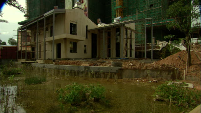 ws pool of stagnant water surrounding base of construction site at vanke town dreamworld complex, shenzhen, guangdong, china - 2008 stock videos and b-roll footage