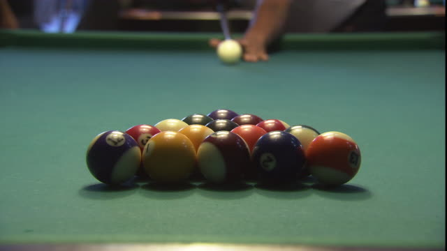 a pool player breaks the rack of balls on a pool table. - キューボール点の映像素材/bロール