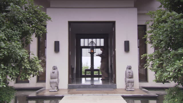 a pool surrounds the entrance of a clubhouse at funchun hotel in shanghai, china. - 美術工芸品点の映像素材/bロール