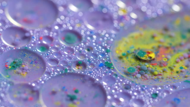 pools of colourful liquid suspended within each other are swirled in a shallow tray. - blob stock videos and b-roll footage