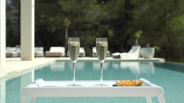 vídeos de stock, filmes e b-roll de poolside champagne centred (jib up) - riqueza