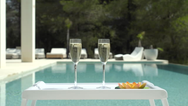 vídeos de stock, filmes e b-roll de poolside champagne centred (jib up) - abundância