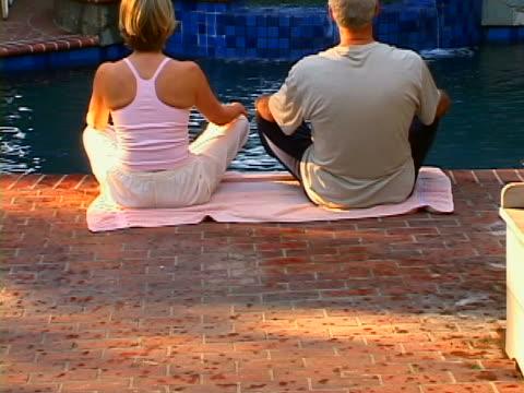 poolside yoga - lotussitz stock-videos und b-roll-filmmaterial