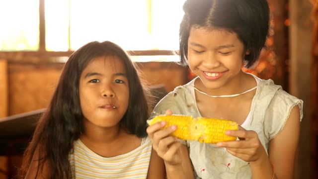 poor asian girls eating corn