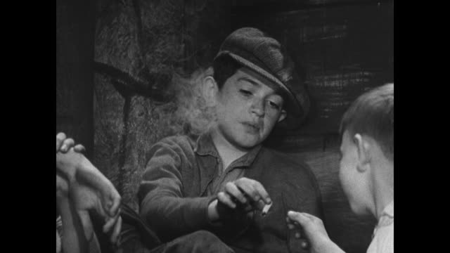 vidéos et rushes de dramatization poor boys gathered at 'alley club' sharing cigarette boys stealing fruit from grocery boy stealing flashlight from department store... - 1936