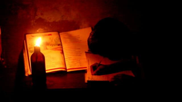 Poor children reading under lantern light