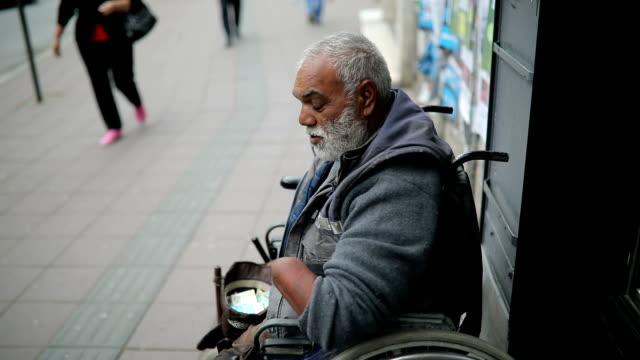 貧しい人々 が通りにお金を求め男を無効に - 依存点の映像素材/bロール