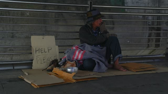 poor homeless man or refugee sitting on the floor on the urban street in the city, social documentary concept, - begging social issue stock videos & royalty-free footage
