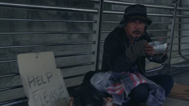 poor homeless man or refugee sitting on the floor on the urban street in the city, social documentary concept, - sad old asian man stock videos & royalty-free footage