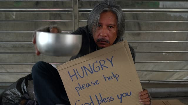 poor homeless man or refugee sitting on the floor on the urban street in the city, social documentary concept, - pleading stock videos & royalty-free footage
