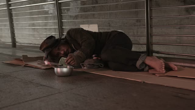 Poor homeless man or refugee sleeping on the floor on the urban street in the city, social documentary concept,