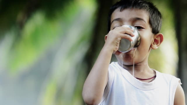 poor Indian little boy drinking water with steelglass