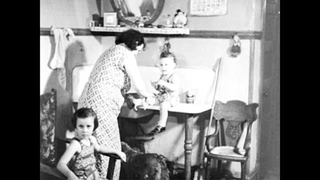/ poor mother washes toddler in sink / other children sitting around dilapidated room / toddler sleeping in cot poverty stricken mother and children... - anno 1960 video stock e b–roll